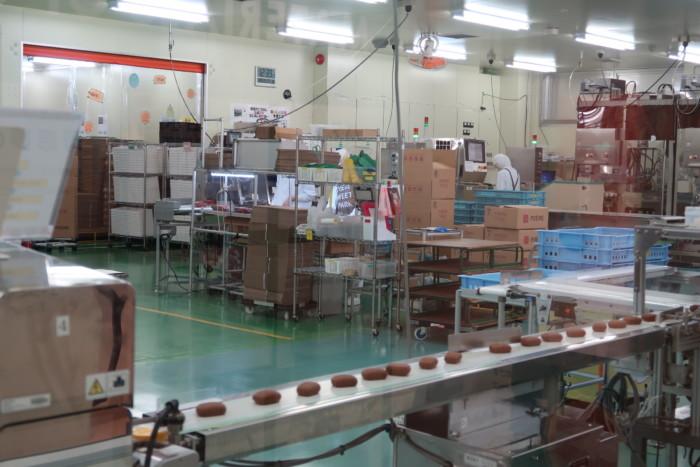 母恵夢スイーツパークの工場見学の様子,ベルトコンベアーで運ばれるショコラ味の母恵夢