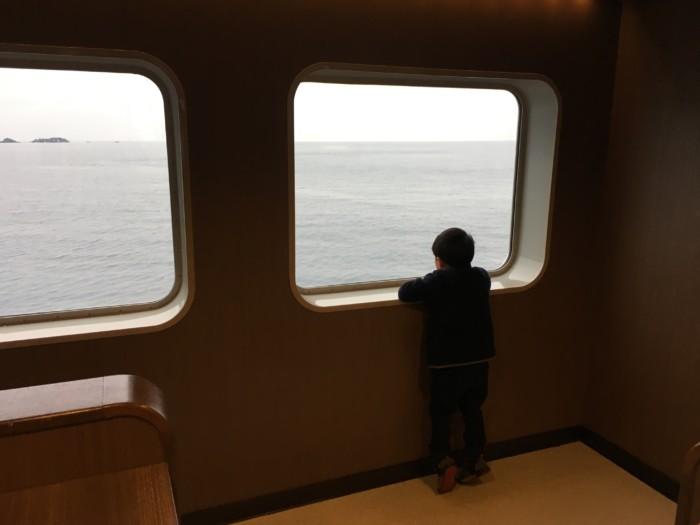 国道九四フェリーの船内から海を見る子供