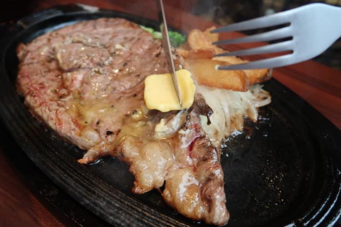 俵屋(今治)の熟成肉ステーキにバターを塗る様子