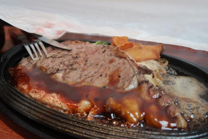 俵屋(今治)の熟成肉ステーキにソースをかける様子